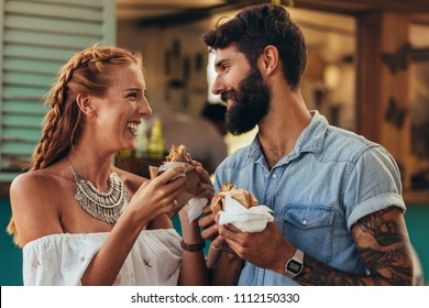 Portrait of happy young couple having burger outdoors. Young man and woman standing near a food truck and eating burger.