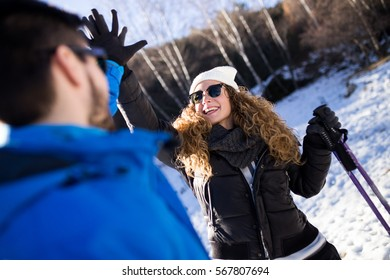 Portrait of happy young couple having fun over winter background.