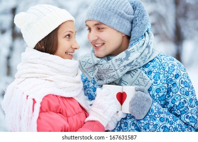 Portrait of happy young couple holding cups with red hearts and toasting in winter park