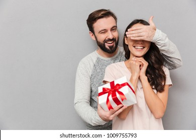 Portrait of a happy young couple hugging while standing together with a present box over gray background, man covers woman's eyes