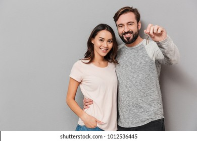 Portrait of a happy young couple hugging and showing house keys over gray background