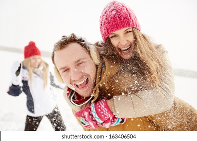 Portrait of happy young couple looking at camera in winter park with their friend behind