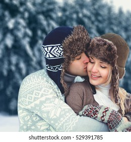 Portrait happy young couple in love at winter day, man gentle kissing woman wearing a hat and knitted sweater, tenderness moment, over snowy trees background