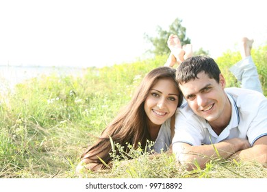 Portrait of a happy young couple lying on grass in a park - Outdoor