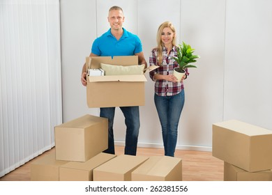 Portrait Of Happy Young Couple Moving Boxes In New Home