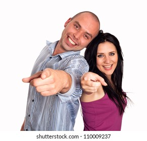 Portrait of happy young couple pointing at you over white background