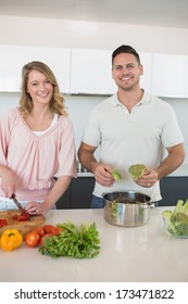 Portrait of happy young couple preparing food at kitchen counter
