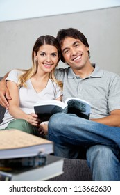 Portrait of happy young couple sitting together on sofa with a book