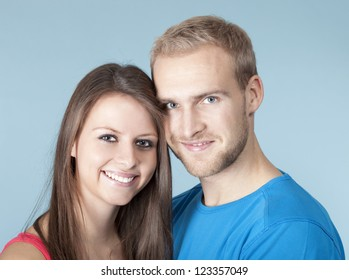 portrait of a happy young couple smiling, looking - isolated on blue