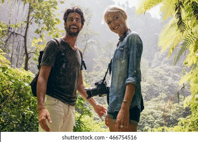 Portrait of happy young couple standing together during rain in the forest. Tourist on hike in forest.