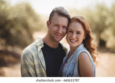 Portrait of happy young couple standing at olive farm on sunny day