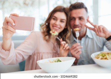 Portrait of a happy young couple taking a selfie while having lunch together at the cafe table indoors