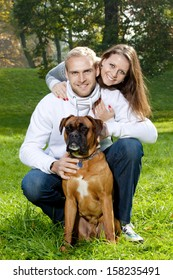 portrait of a happy young couple with their dog in the park.