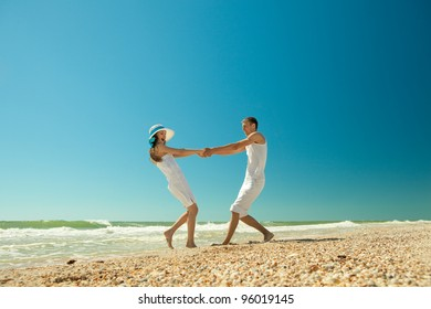 Portrait of a happy young couple twirling on the beach. Couple enjoying a summer vacation.