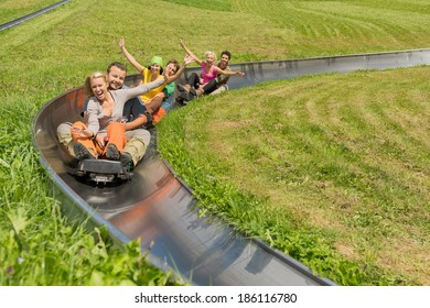 Portrait of happy young couples enjoying summer sledge ride