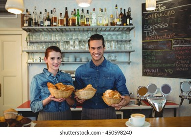 Portrait of happy young co-workers with fresh breads in basket at cafe
