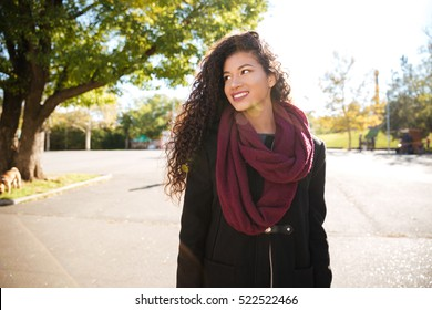 Portrait of happy young dark skinned curly woman wearing scarf smiling against nature background. Look aside.