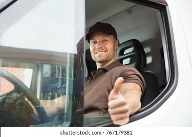 Portrait Of A Happy Young Delivery Man Sitting Inside Van