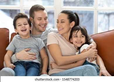 Portrait of happy young family with little preschooler kids sit on couch hug show love and care, smiling parents embrace cuddle with small children relaxing on couch at home together, bonding concept