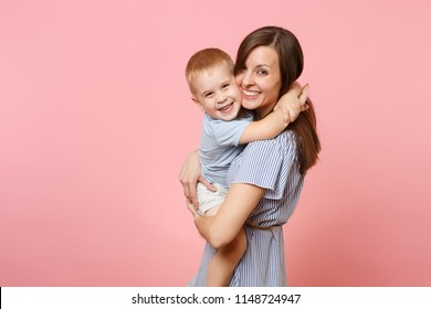 Portrait happy young family. Mother keep in arms, tender embrace, gently hugs child kid son baby boy on pastel pink background. Sincere emotions, fondness, Mother's Day, parenthood, childhood concept