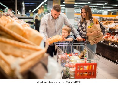 Portrait of happy young family  shopping for groceries in supermarket together with little boy, while choosing fresh bread loaf in bakery department