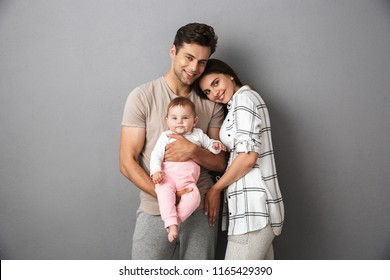 Portrait of a happy young family with their little baby girl isolated over gray background, hugging