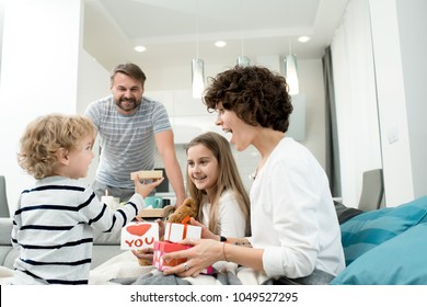 Portrait of happy young family with two children celebrating Valentines day  at home with adorable little boy giving presents in foreground