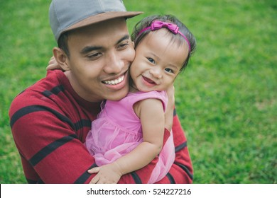 portrait of Happy young father with little daughter outdoors