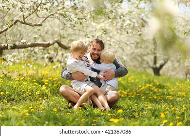 A portrait of a happy young father tickling and laughing with his two young boy children under the white flowering trees on a spring day.