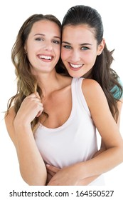 Portrait of happy young female embracing her friend from behind over white background