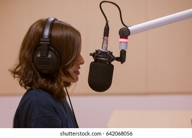 Portrait of happy young female radio host broadcasting in studio