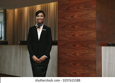 Portrait of happy young female receptionist standing at hotel front desk to welcome guest. Female concierge welcoming guest in hotel.