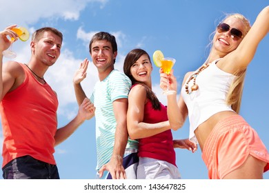 Portrait of happy young friends with cocktails having beach party