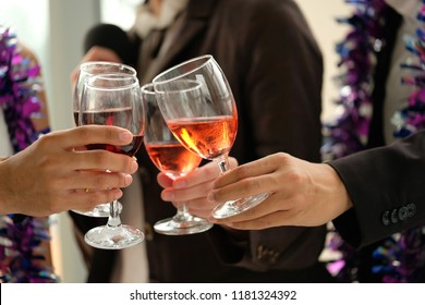 Portrait of happy young friends having fun and drinking together afterwork party.Hands holding the glasses of drink making a toast or celebration. Party ,congratulation concept.