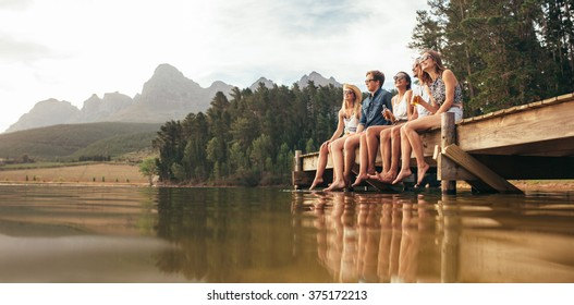 Portrait of happy young friends sitting on pier at the lake drinking beers. Young men and woman enjoying a day at the lake.
