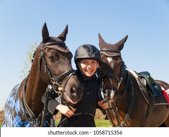 Portrait of happy young girl after winning the showjumping competition with her two horses