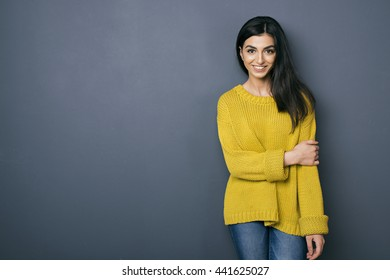 Portrait of happy young girl in bright sweater against of grey wall.