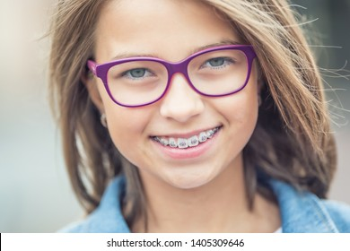 Portrait of happy young girl with dental braces and glasses.