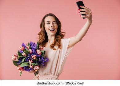 Portrait of a happy young girl in dress taking selfie with mobile phone while holding big bouquet of irises and tulips isolated over pink background