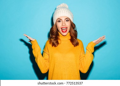 Portrait of a happy young girl dressed in winter clothes standing with outsretched hands isolated over blue background