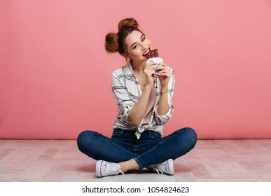 Portrait of a happy young girl eating chocolate bar while sitting on a floor with legs crossed isolated over pink background