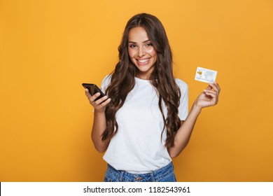 Portrait of a happy young girl with long brunette hair standing over yellow background, holding mobile phone, showing plastic credit card