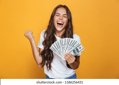 Portrait of a happy young girl with long brunette hair standing over yellow background, holding money banknotes, celebrating