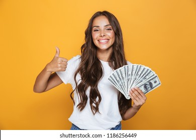 Portrait of a happy young girl with long brunette hair standing over yellow background, holding money banknotes, showing thumbs up