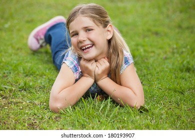 Portrait of a happy young girl lying on grass at the park