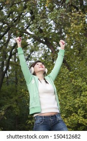 Portrait of happy young girl raised hands to the sky in the forest