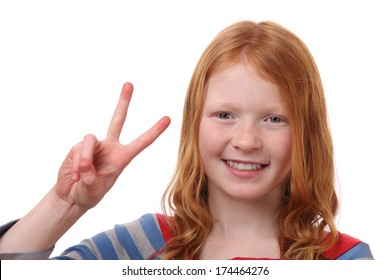 Portrait of a happy young girl showing victory sign on white background