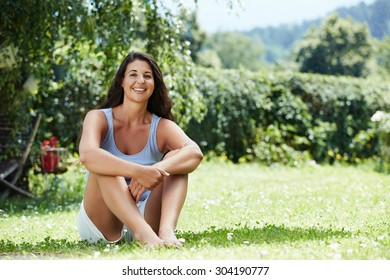 Portrait of a happy young girl sitting in the gras in her garden