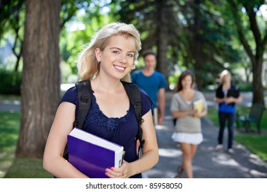 Portrait of happy young girl smiling while her classmates walking in background