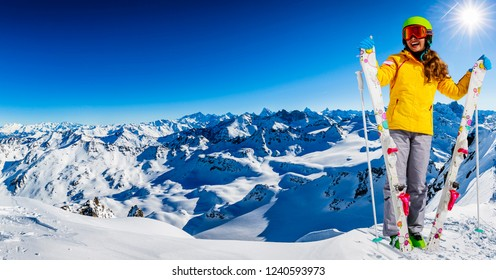 Portrait of happy young girl standing in the snow with ski in winter time, ski slope in the background.